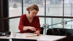Emila Hoving sitter vid ett bord och studerar ett orkesterpartitur, med stora glasfönster i bakgrunden.