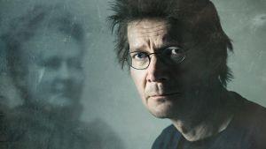 Juha Hurme katsoo kameraan taustallaan kuva, jossa näkyy sumea Minna Canth