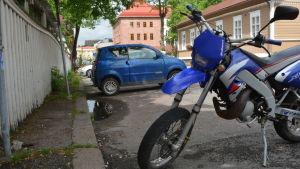 En blå mopedbil och en blå moped står på en parkeringsplats i centrala Borgå.