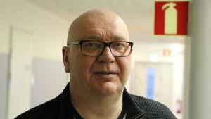 En medelålders flintskallig man med glasögon står i en vit korridor.