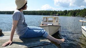 Kvinna sitter på brygga, i bakgrunden en båt.