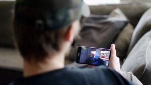 Ung man tittar på mobiltelefonens skärm.