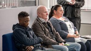 Poika, mies ja nainen istuvat jonkinlaisella odotuspenkillä.