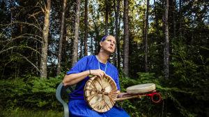 Fintiaani Lyz Jaakola istuu metsässä rumpujensa kanssa.