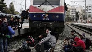 Flyktingar sitter på järnvägsspåren på järnvägsstationen Larissa i Aten på fredagen 5.4.2019.