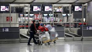 Arbetare samlar ihop saker på den gamla flygplatsen.
