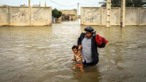 En iransk man bär sin son i staden an Ahvaz, Iran.