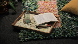 En bricka med en flaska och böcker som en del av en inredd balkong.