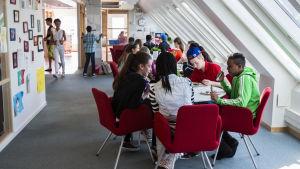 skolelever sitter och står i ett rum med fönster i snedtak. Röda stolar på blå heltäckande matta