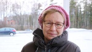 En kvinna i 60-årsåldern med en rosa mössa på huvudet står på en parkeringsplats.