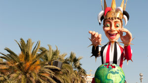 Suuri, ilmalla täytetty narrihahmo kulkee palmujen katveessa Nizzan rantabulevardilla.