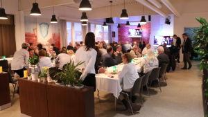 Tiotals människor sitter vid sina bord i en restaurang.