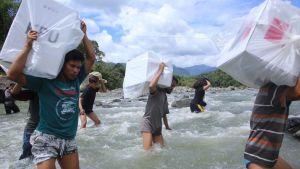 Indonesier transporterar valurnor över ett vattendrag.