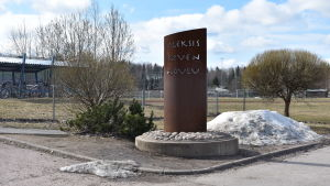 Skylt där det står Aleksis Kiven koulu. Skylten är vid en gräsplan och grusväg.