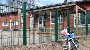 En cykel står parkerad utanför en lekplats vid en röd daghemsbyggnad.