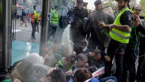 Fransk kravallpolis använder pepparspray mot demonstranter som blockerar entrén till banken Société Générales högkvarter.