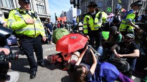 Polisen försöker gripa demonstranter i London 19.4.2019. Demonstranter rör sig för femte dagen i rad på gatorna i London.