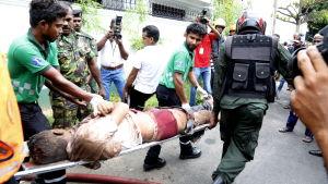 Ett offer slussas på bår i Colombo efter terrorattacken den 21 april 2019.