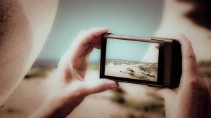 En person tar ett fotografi med en mobiltelefon.