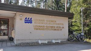 En tegelhusvägg med texten Lounais-Suomen vesi- ja ympäristötutkimus Oy