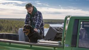 """Mies istuu """"pickup truck"""" -pakun reunalla ja silittää koiraa. Taustalla näkyy metsämaisema ja järvi."""