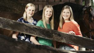 Kolme nuorehkoa naista katsoo kameraan ja hymyilee. Heidän takanaan seisoo hevonen.