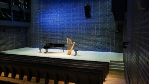 A grand piano and a harp on a stage in Musiikkitalo.