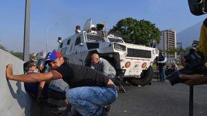Människor söker skydd under en eldstrid mellan oppositionsanhängare och regeringstrogna soldater i Caracas