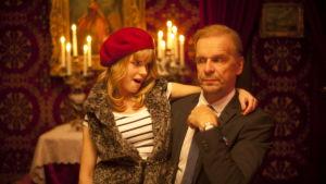 Nuori tyttö (Iida Lampela) istuu vanhemman miehen (Jukka Puotila) sylissä ja katsoo häntä haastavasti.