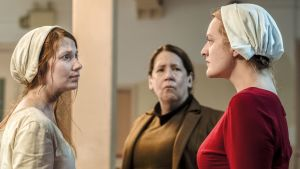 Kolme naista seisovat ja katsovat toisiaan.