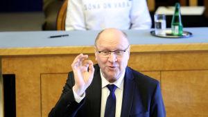 Mart Helme står och pratar. Bakom honom skymtar Estlands president i en vit tröja som hon bär i protest mot minskad pressfrihet