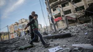 En palestinsk pojke och hans mamma går bland bråtet efter en flygattack i Gaza City på söndagen.