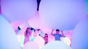 Lapset kannattelevat valtavia värikkäitä ilmapalloja