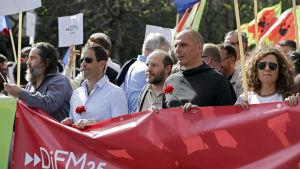 Greklands tidigare finansminister Yanis Varoufakis håller en Diem 25-banderoll under en demonstration i Portugal.