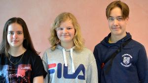 Porträtt av tre skolelever, två flickor och en pojke.