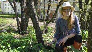 Alessandra Sarelin plockar kirskål i sin trädgård.