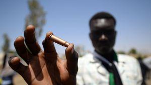 En demonsrant visade upp en hylsa utanför arméhögkvarteret i Khartoum efter våldet där i början av veckan.