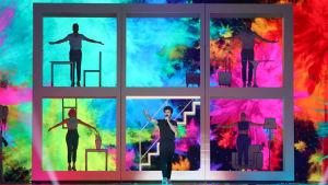 miki uppträder för spanien med färgglad bakgrund och ett stort fönster med sångare i i bakgrunden