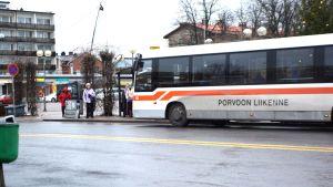 En buss som det står Porvoon Liikenne på står vid en hållplats på torget i Borgå. Några personer ska stiga på.