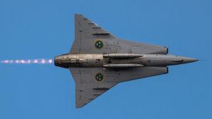 Ruotsalainen hävittäjä Draken J-35 lentää sinistä taivasta vasten.