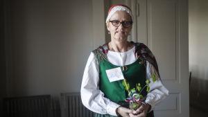 En kvinna står inne i ett hus. Hon har på sig en traditionell folkdräkt. I handen har hon en glasburk med en björkkvist och Serbiens flagga.