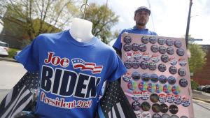 """En man står och säljer blåa skjortor med texten """"Joe Biden president 2020""""."""