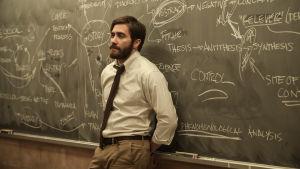 Mies nojaa isoa liitutaulua vasten oletettavasti jonkinlaisessa luokkahuoneessa.