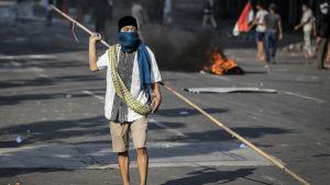 En demonstrant som beväpnat sig med en lång bambukäpp under sammandrabbingarna i Jakarta