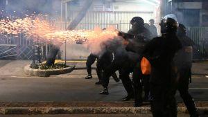 En kravallutrustad polis avfyrar tårgas under oroligheterna i Jakarta