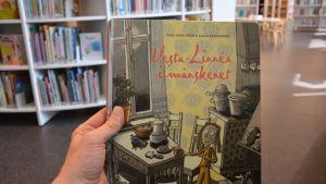 """I ett bibliotek håller en hand i boken """"Vesta-Linnéa i månskenet""""."""