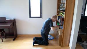 Henrik Gustafsson på knä i sitt hem, gräver i sin cd-hylla.
