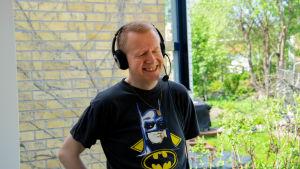 henrik Gustafsson leende på sin balkong med headet på huvudet. Vårgrönska i bakgrunden.