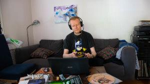 henrik Gustafsson med headset på huvudet sitter vid latop i sitt vardagsrum med skivor omkring sig.