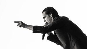 Svartvit bild på Nick Cave i mörk kostym live mot en vit himmel. Cave i profil pekar med fingret framåt.